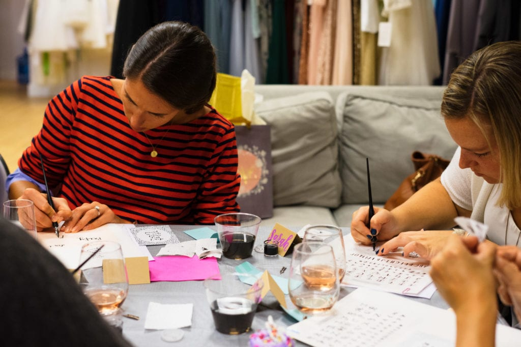 DIY Bride learning Sip & Script Calligraphy class at bella bridesmaids